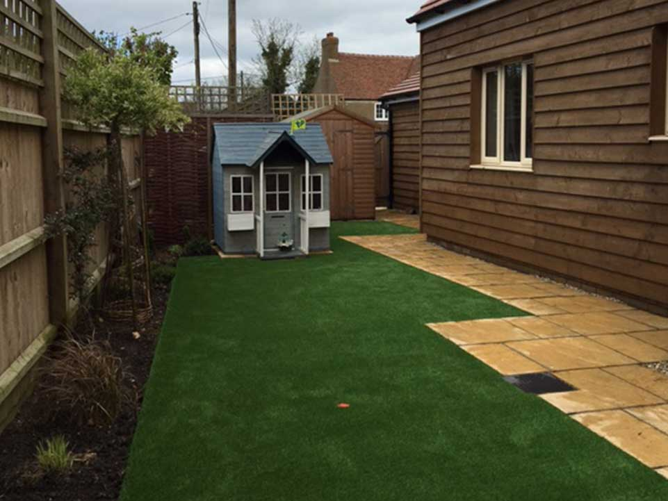 Artificial grass, paving slabs, and play house